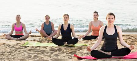 smiling italian  sporty females meditating in yoga position Padmasana on seaside Stock Photo