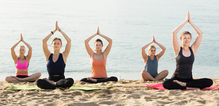 equilibrium: Adult women making yoga meditation in lotus pose on sunny beach by ocean