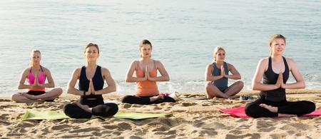 Nice women making yoga meditation in lotus pose on sunny beach by ocean