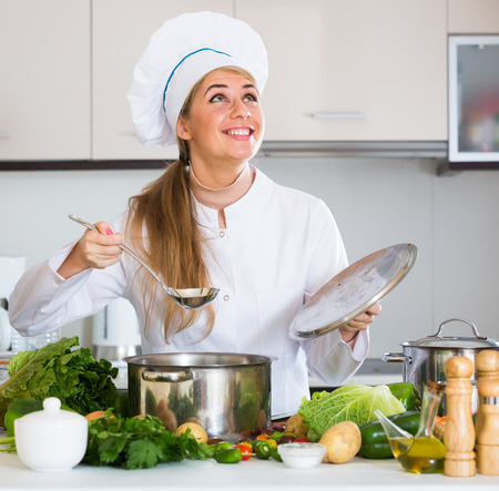 25s: Cheerful female chef making vegetarian meal with vegetables