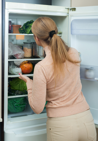 25s: Adult ordinary blonde looking at products in refrigerator