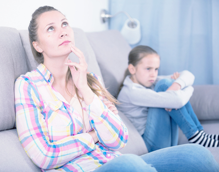 Young sad mother quarreled with schoolgirl daughter at home Stock Photo