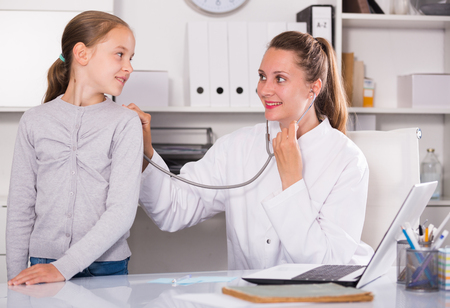 Young female doctor leading medical appointment the girl with stethoscope