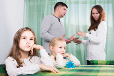 Unhappy european  family with two little children  having conflict at home. Focus on girls Stock Photo