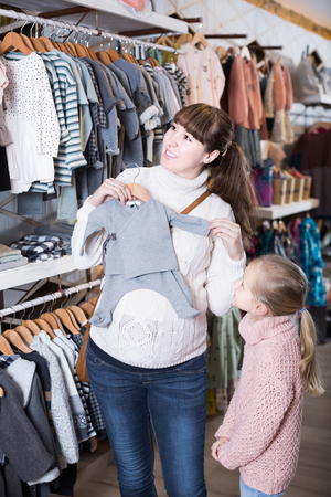 romper: happy english pregnant mother and daughter choosing romper suit for baby in children�s clothes shop