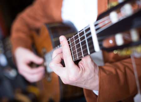 Image of hands of man in jacket playing an acoustic guitar Reklamní fotografie - 81568671