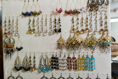 Lot of colored earrings hanging on the stand in the store