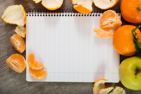Notebook in line and fruits on table