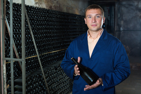 laboratorian: Adult male winery technician posing with bottle of wine in cellar