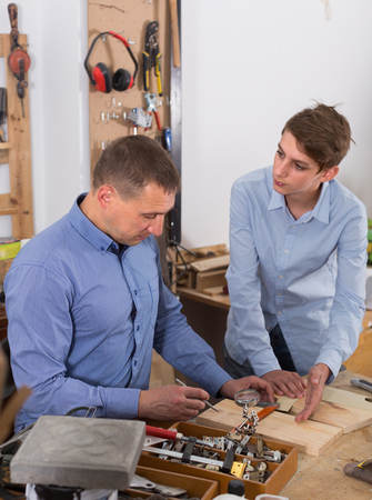 toolroom: happy american father and teen son working with wood plank in workshop Stock Photo