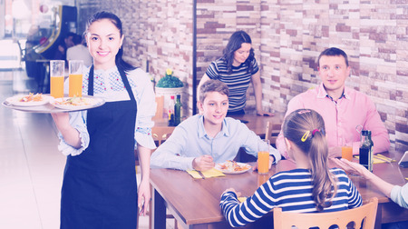 bringing: happy young waitress warmly welcoming guests to comfortable family cafe Stock Photo