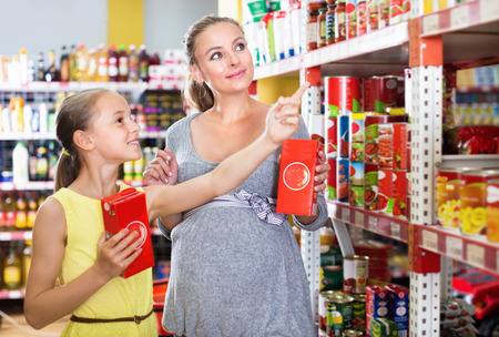 store shelf: Glad cheerful positive woman with daughter are choosing fresh goods in food department in supermarket