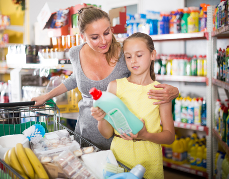 Teenage girl is showing chosen purchases from trolley in supermarket.