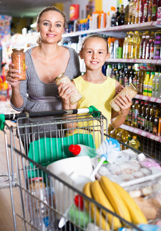choise: Happy  mother with teenage girl demonstrating their choise in food department in supermarket Stock Photo