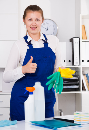 office cleanup: Cheerful female cleaner is satisfied after cleaning in the office.