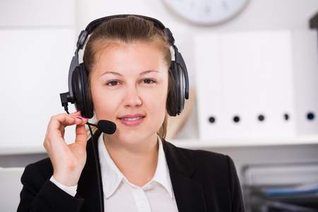 dispatcher: Portrait of operator in black suit which is talking by headset with client in the office.