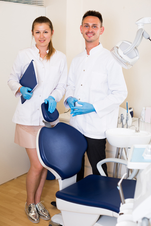 Profi in Uniform mit seinem Assistent treffen sich nächste Klient in der Klinik.