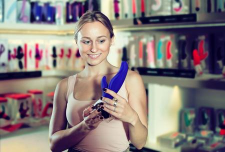 Positieve vrouwelijke klant winkelen seks speelgoed in seks winkel