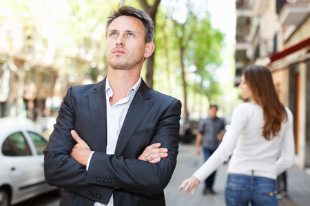 Annoyed guy on departing girlfriend background after quarrel outdoors
