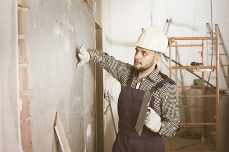 home decorating: Male builder is checking the quality of the work done after the plaster wall at home.