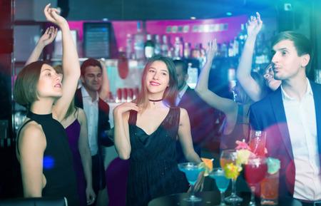 Contentos colegas bailando en fiesta corporativa con cócteles en las manos.