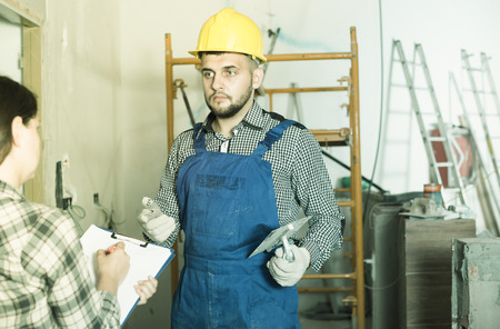 clarifying: Worker in helmet with spatula is clarifying details from client at home. Stock Photo