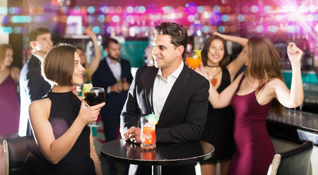 feast: Positive young females and males celebrating corporate in the bar at night