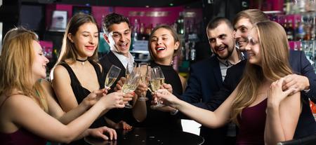 Freundliche Kollegen, die auf Firmenparty mit Cocktails tanzen