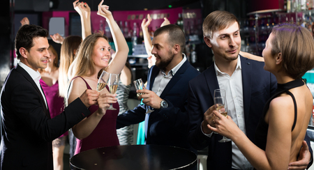 feast: Portrait of smiling office workers with champagne in the night club