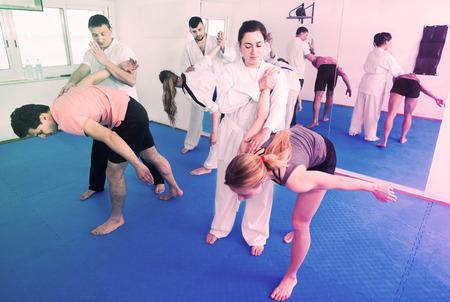 Young adults practicing new taekwondo holds in pairs in class Stock Photo