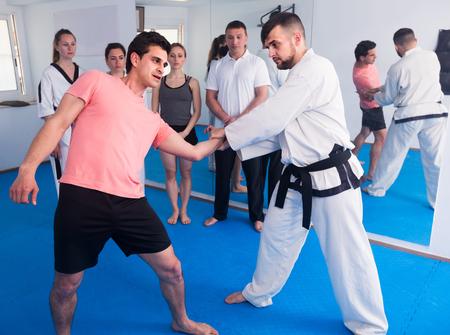 happy spanish man training new taekwondo holds with adults during class Stock Photo