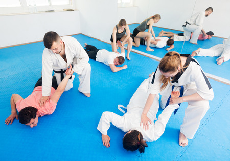 Cheerful adults training in pairs to practice new holds at taekwondo class