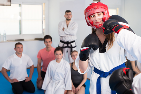 Pair of young women exercising new taekwondo techniques during class