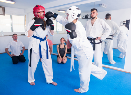 Adult girls are sparring in pair to use taekwondo technique during class. Stock Photo