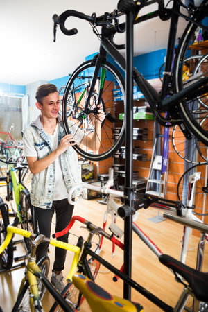 Smiling boy teenager purchasing new bicycle in sport hypermarket