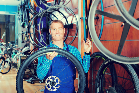 Smiling man seller in uniform working with new bicycle wheel in sport hypermarket Stock Photo