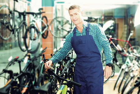 Smiling man seller in uniform holding bicycle in sport hypermarket Stock Photo