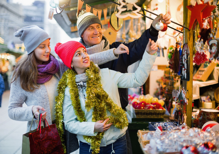 Happy smiling cheerful  family of three at Christmas market. Selective focus