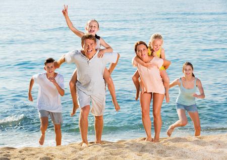 Vriendelijke, positieve familie van zes mensen die graag hardlopen en kinderen op ouders meenemen op het strand