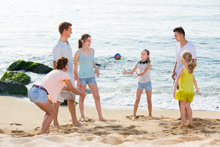 dug: Large happy family of six people playing active games on beach together