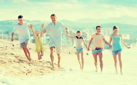 Large carefree family of six people happily running together on beach on summer day Stock Photo