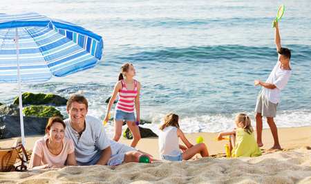 dug: Friendly  couple relaxing on beach while their four kids playing active games and sand on summer day Stock Photo