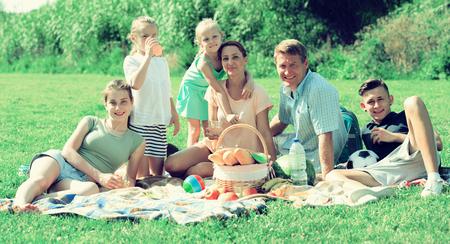 Gelukkige ouders met vier jonge geitjes in verschillende leeftijd die picknick hebben in openlucht op zonnige dag Stockfoto