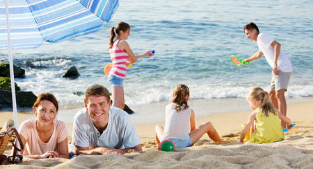 Smiling friendly positive couple relaxing on beach while their four kids playing active games and sand on summer day Stock Photo