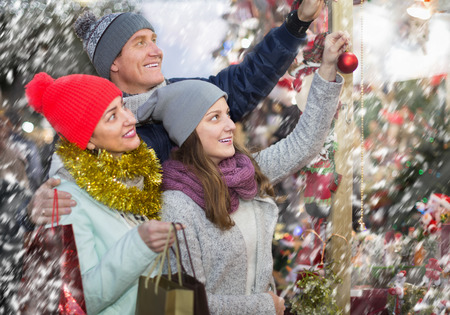 festal: interested family couple with teen daughter choosing Christmas decoration at fair