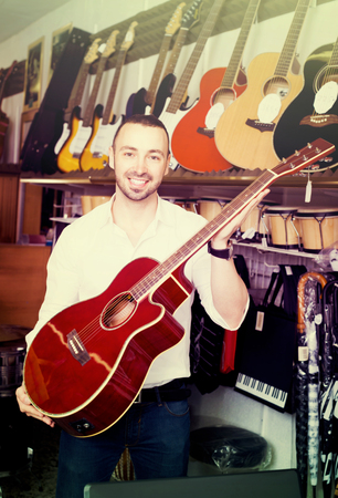 Young man 30s  in white shirt selecting classical guitar at studio Stock Photo