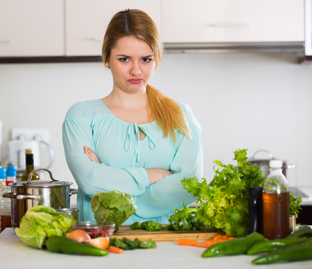 Female tired of vegetarian meal standing at kitchen table