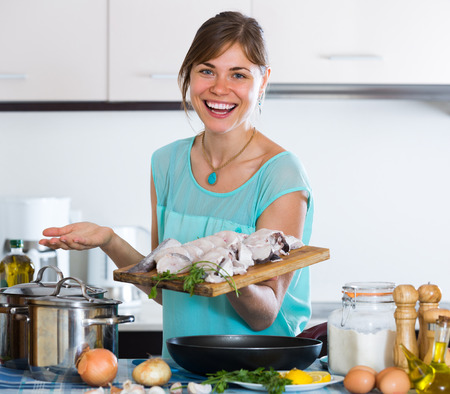 Cheerful smiling adult girl at kitchen putting fish in frying pan Stock Photo
