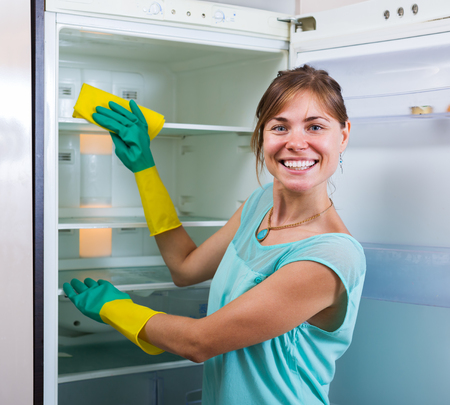 refrigerator: Positive housewife washing fridge with a detergent at the home kitchen