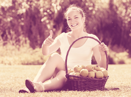 Happy young girl with basket of harvested apples in garden Stock Photo